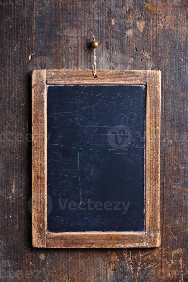 Nahaufnahme einer Schieferkreidetafel, die an einer Holzwand hängt foto