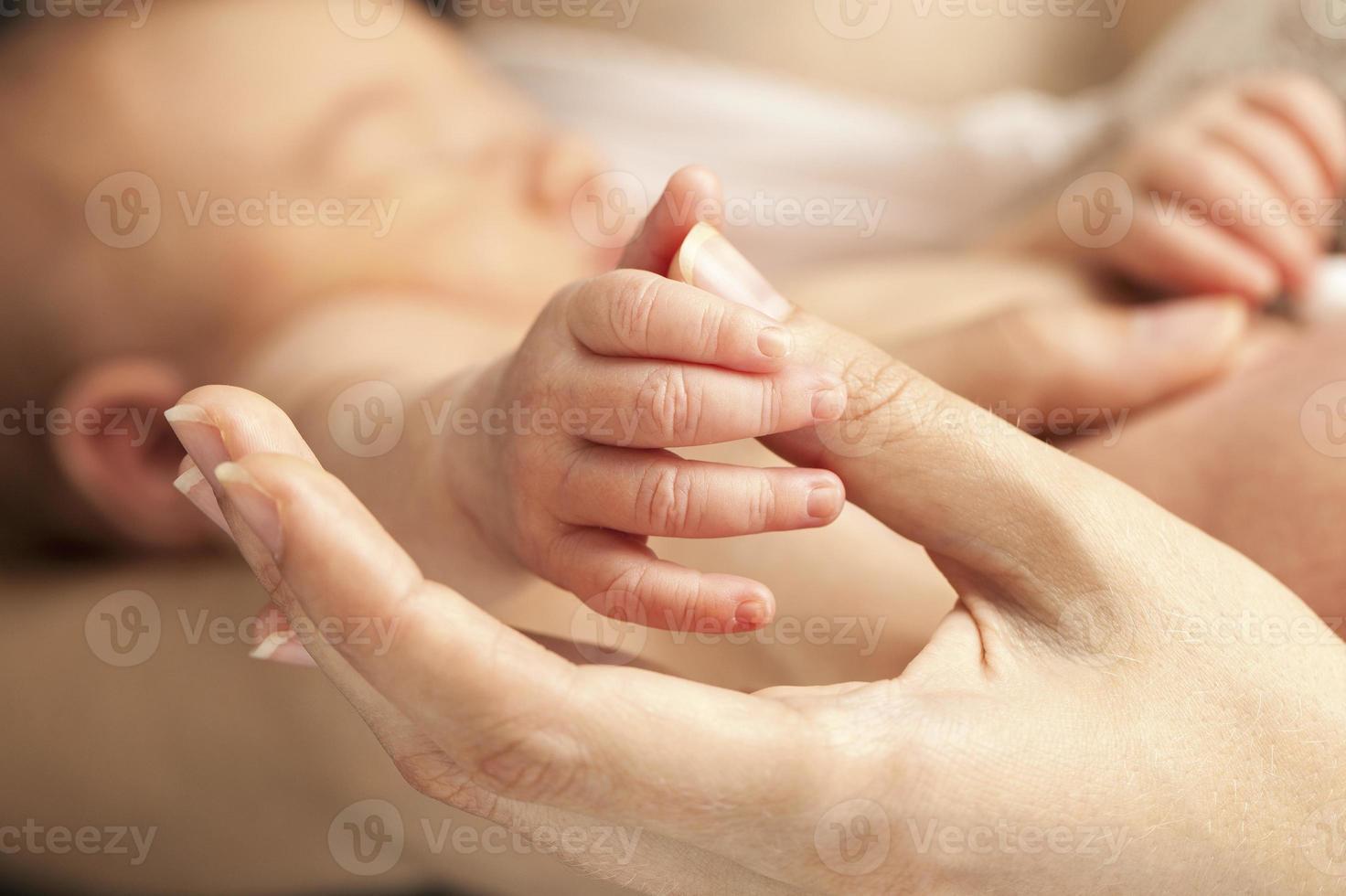 Die Hand des Neugeborenen hält den Daumen der Mutter foto