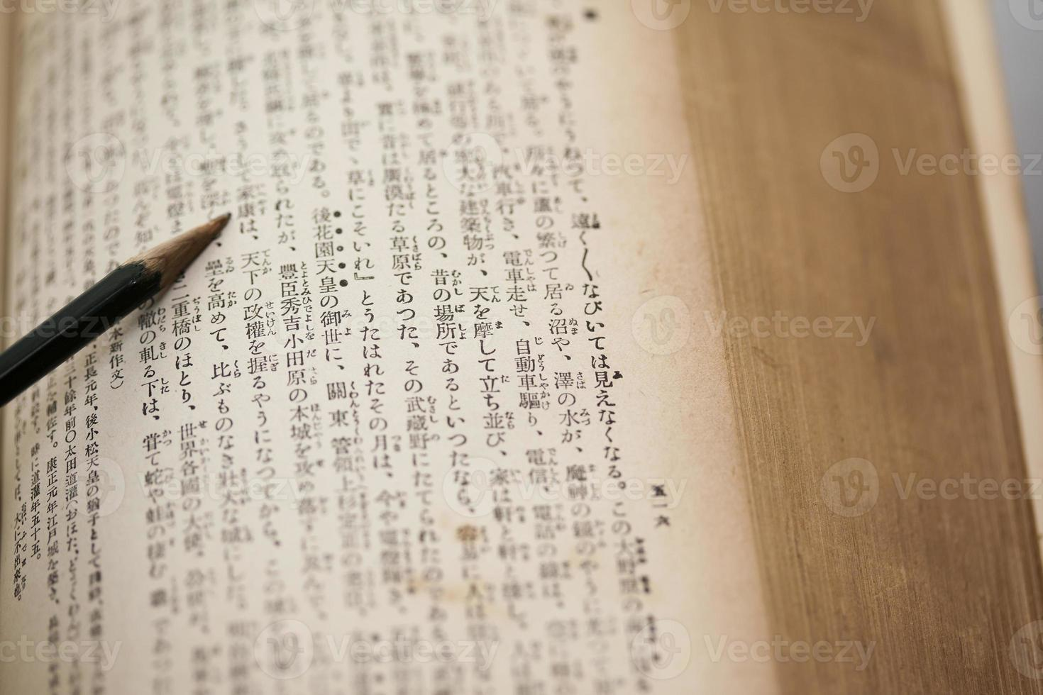 verfärbtes altes japanisches Buch und Bleistift foto