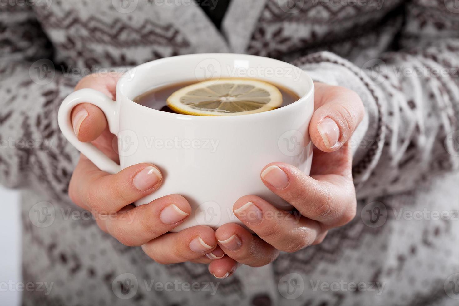 Hände halten eine Tasse Tee foto
