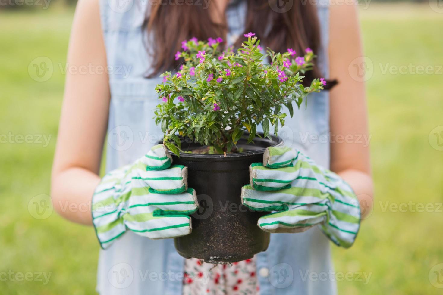 glückliche Frau, die Topfblumen hält foto