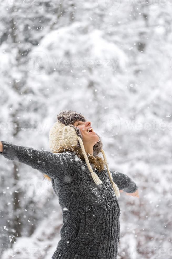 glückliche Frau beim fallenden Schnee mit offenen Armen foto