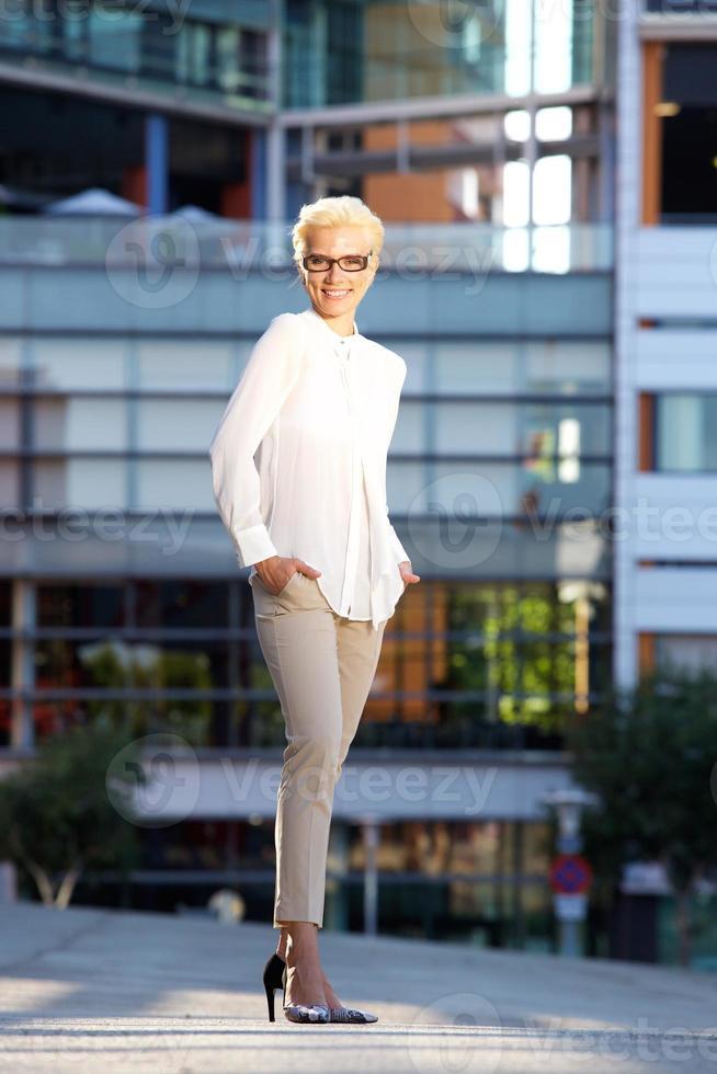 lächelndes Model mit Brille draußen stehend foto