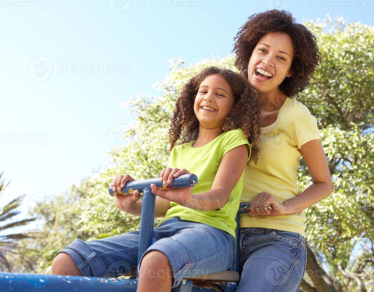 Mutter und Tochter reiten auf Wippe im Park foto