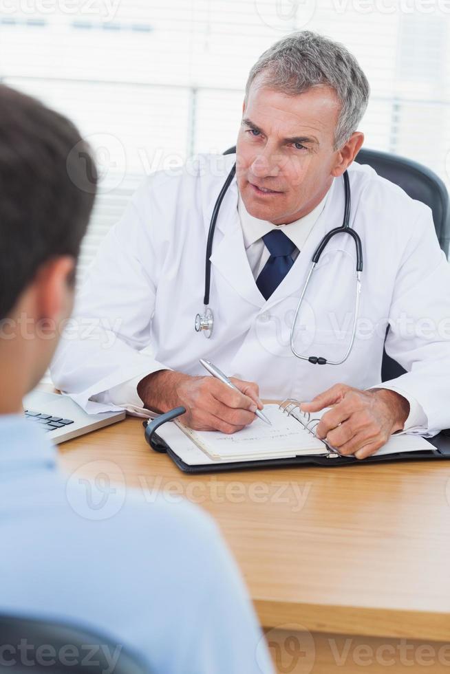 ernsthafter Arzt, der seinem Patienten ein Medikament verschreibt foto