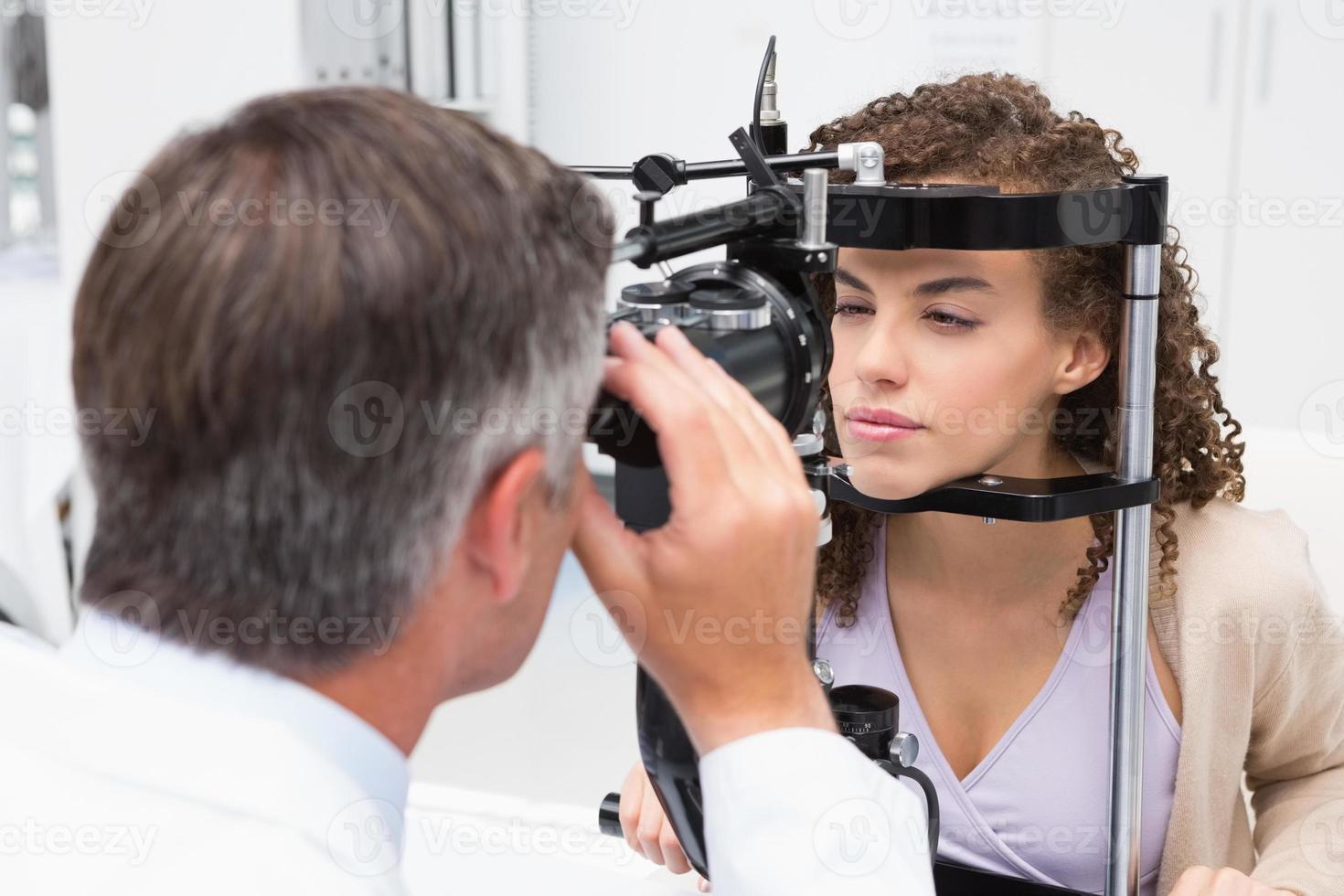 Frau macht Sehtest mit Optiker foto