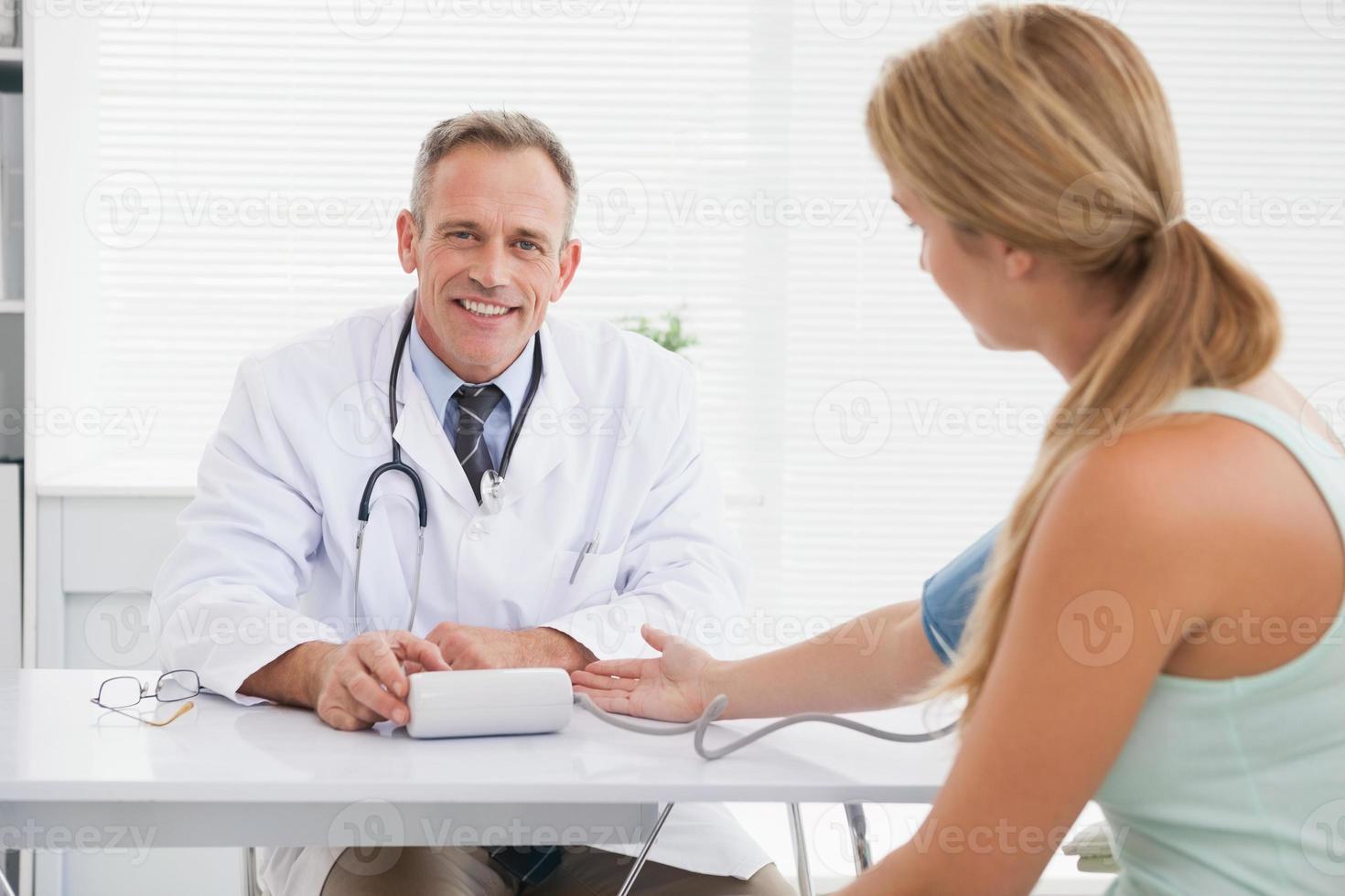 lächelnder Arzt, der Patientenblutdruck nimmt foto