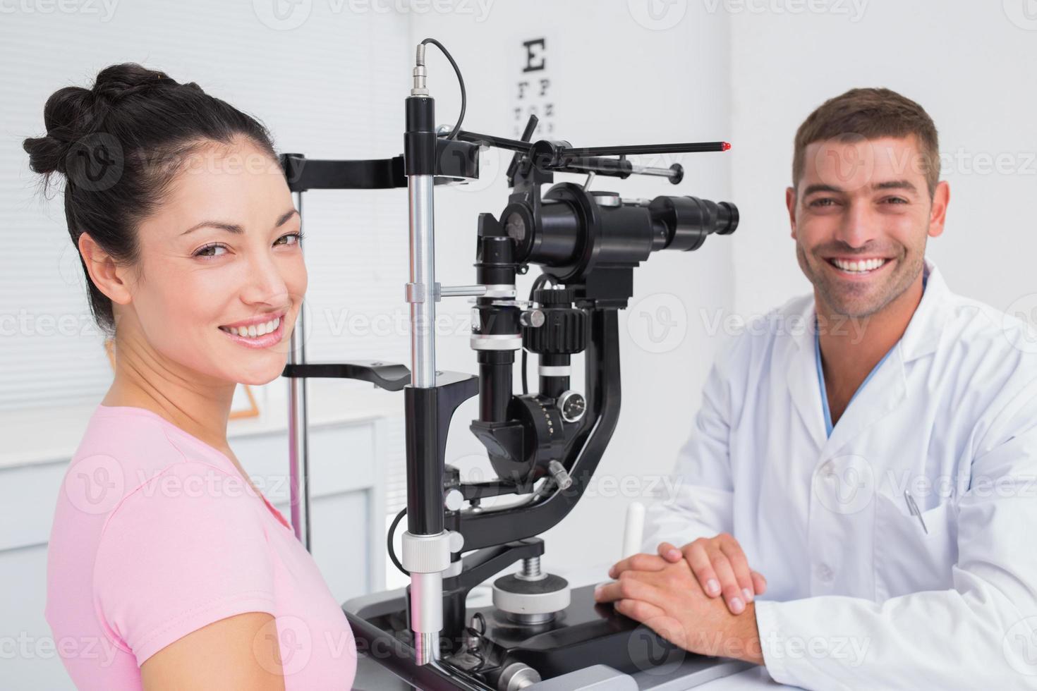 glücklicher Optiker und Patientin mit Spaltlampe foto