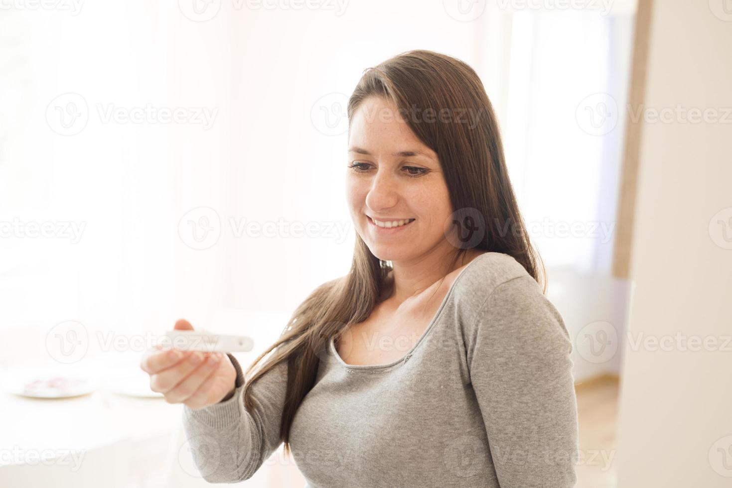 Frau mit Schwangerschaftstest foto
