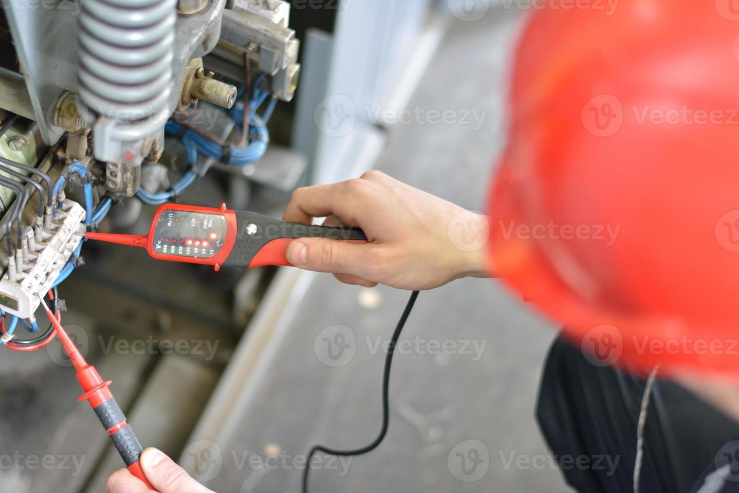 Elektriker prüft auf Spannung am Klemmenblock foto