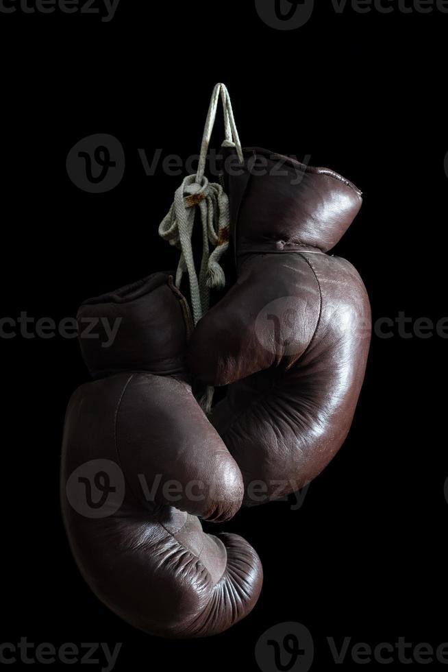 alte Boxhandschuhe, hängend, lokalisiert auf schwarzem Hintergrund foto