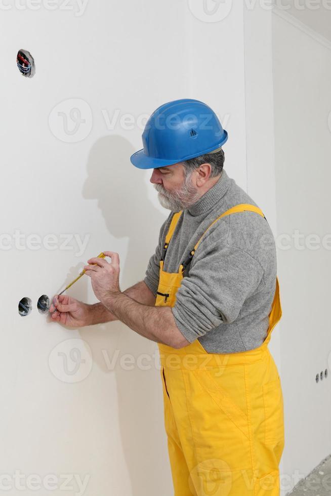 Elektriker auf der Baustelle prüft Installation foto