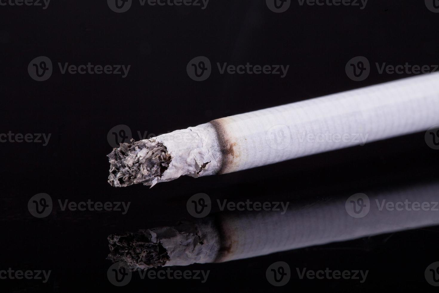 einzelne brennende Zigarette mit Asche lokalisiert auf schwarzem Hintergrund foto