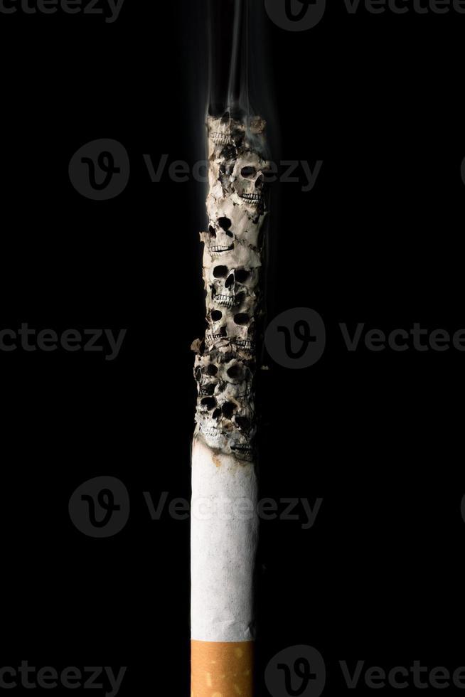 brennende Zigarette mit Schädeln und Asche foto