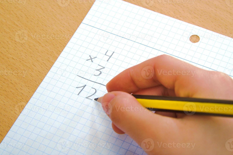 Kind macht eine mathematische Multiplikation als Hausaufgabe foto