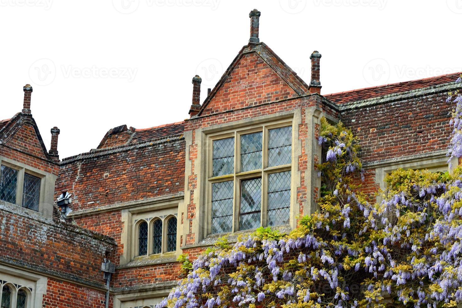 großes Tudorgebäude mit Glyzinien foto