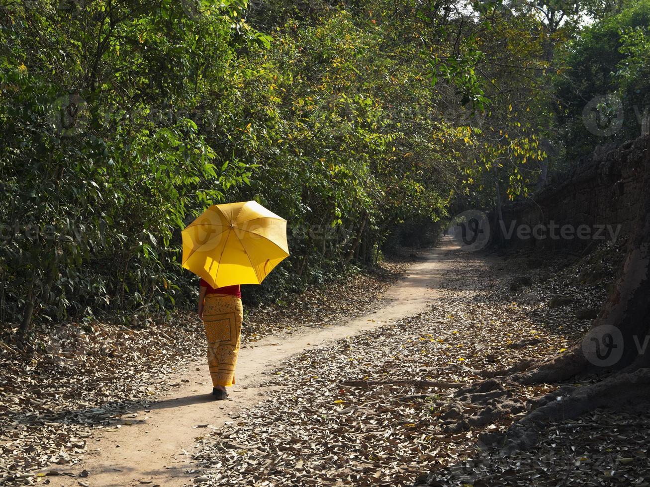 Mädchen, das entlang eines bewaldeten Weges geht foto
