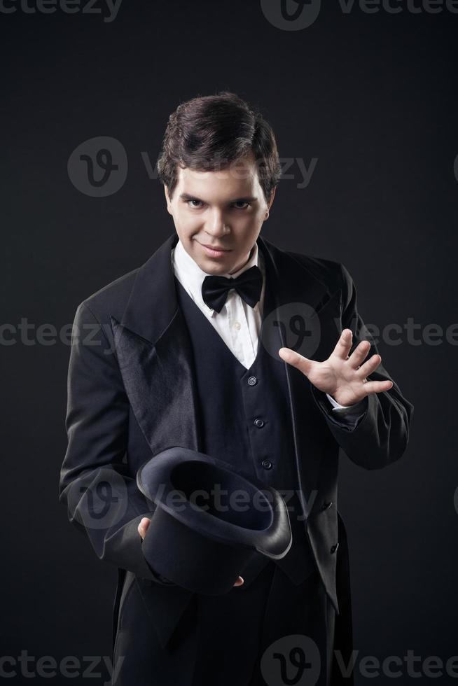 Zauberer zeigt Tricks mit Zylinder lokalisiert auf dunklem Hintergrund foto