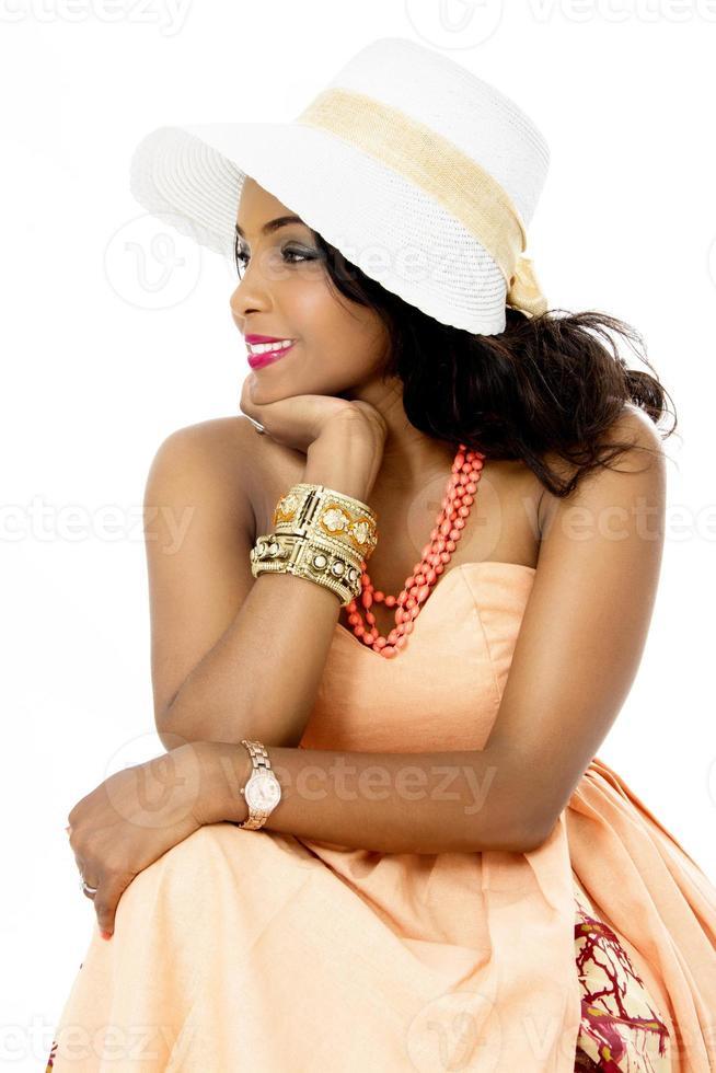 schönes junges afrikanisches weibliches Modell, sitzend, seitwärts schauend, isoliert foto