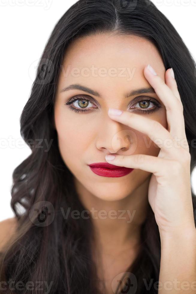 dunkelhaariges Modell mit roten Lippen, die ihr Gesicht verstecken foto