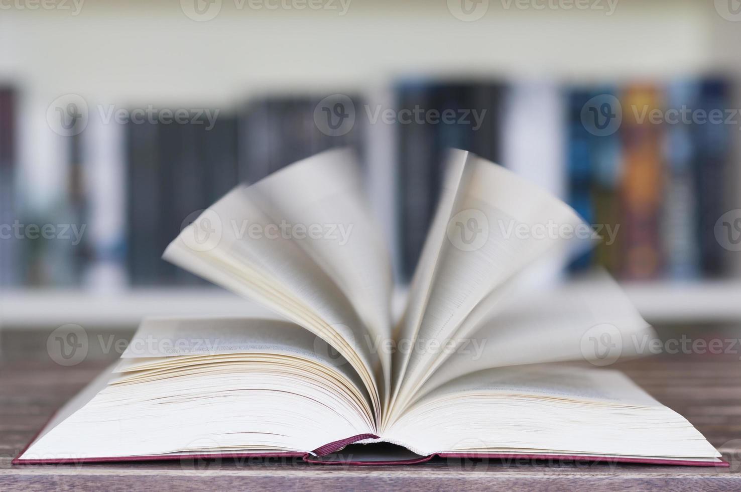 geöffnetes Buch vor dem Bücherregal foto