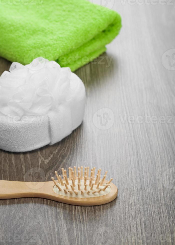 Haarbürste und Badeschwamm mit grünem Handtuch foto