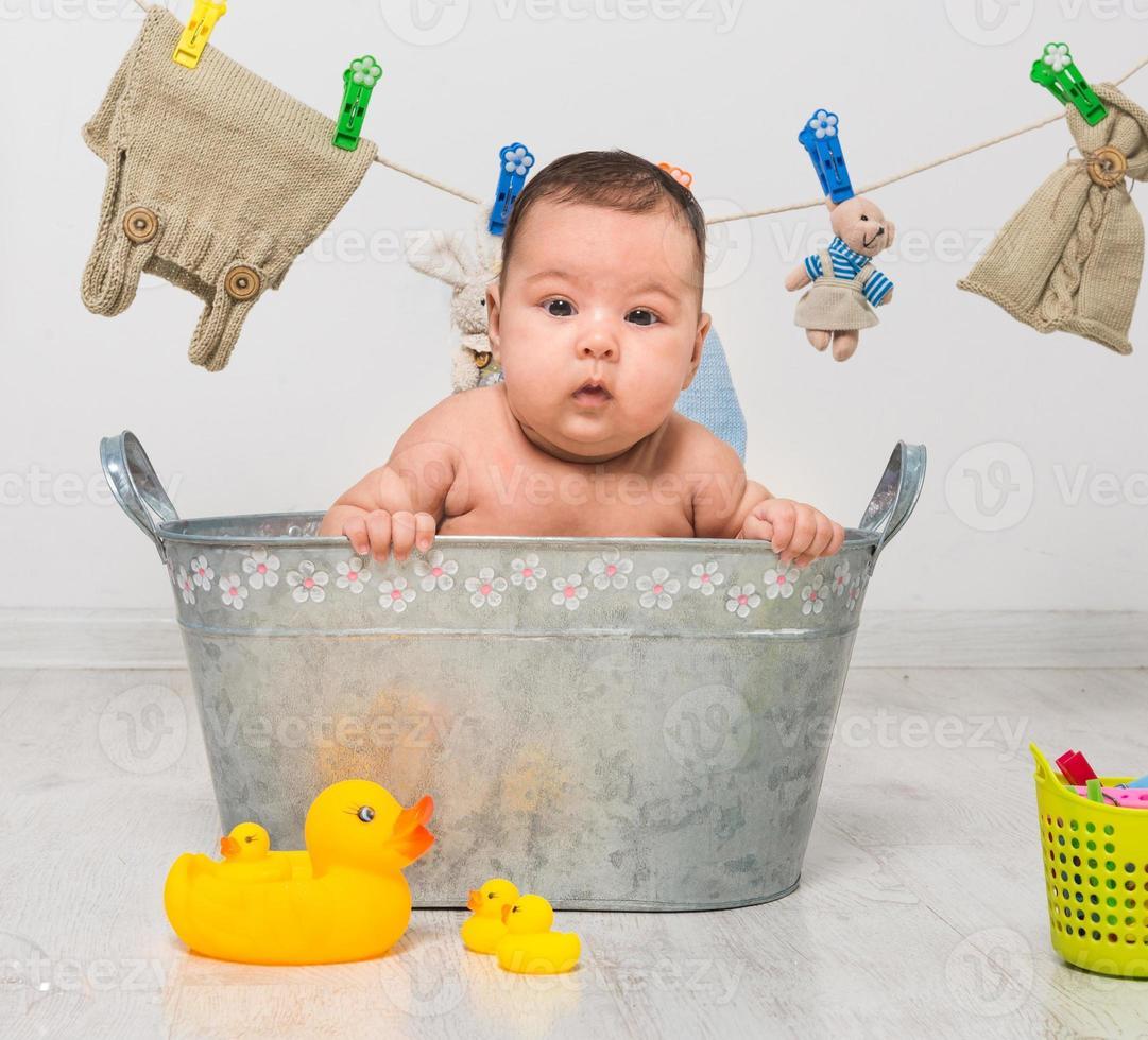 Baby badet in einem Trog foto