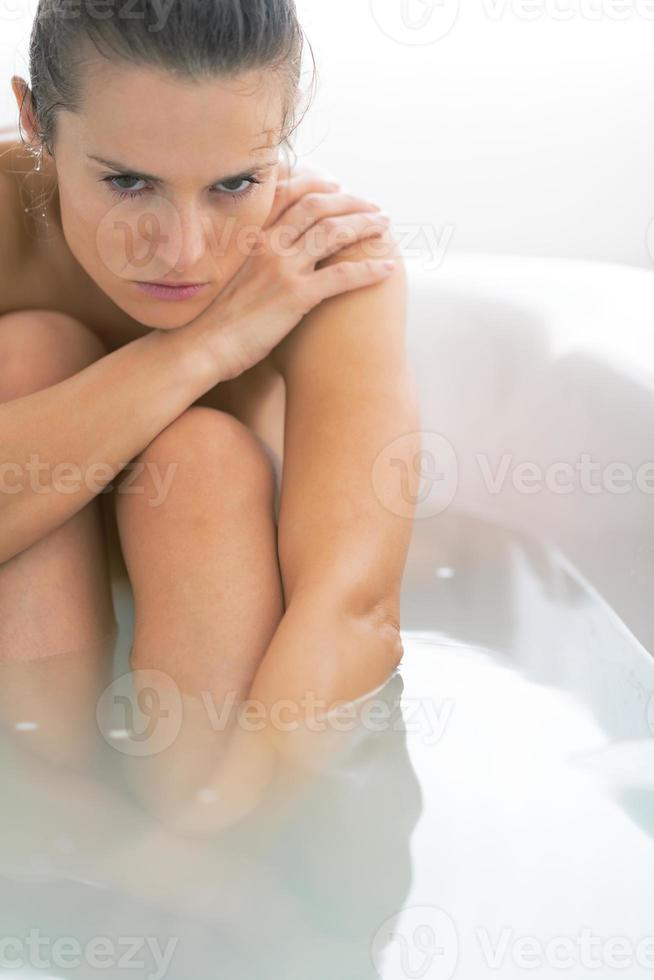 gestresste junge Frau sitzt in der Badewanne foto