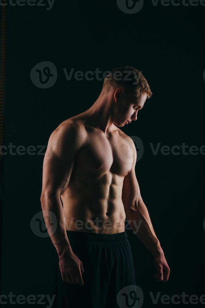 muskulöser junger Mann, der seinen Bizeps lokalisiert auf schwarzem Hintergrund zeigt foto