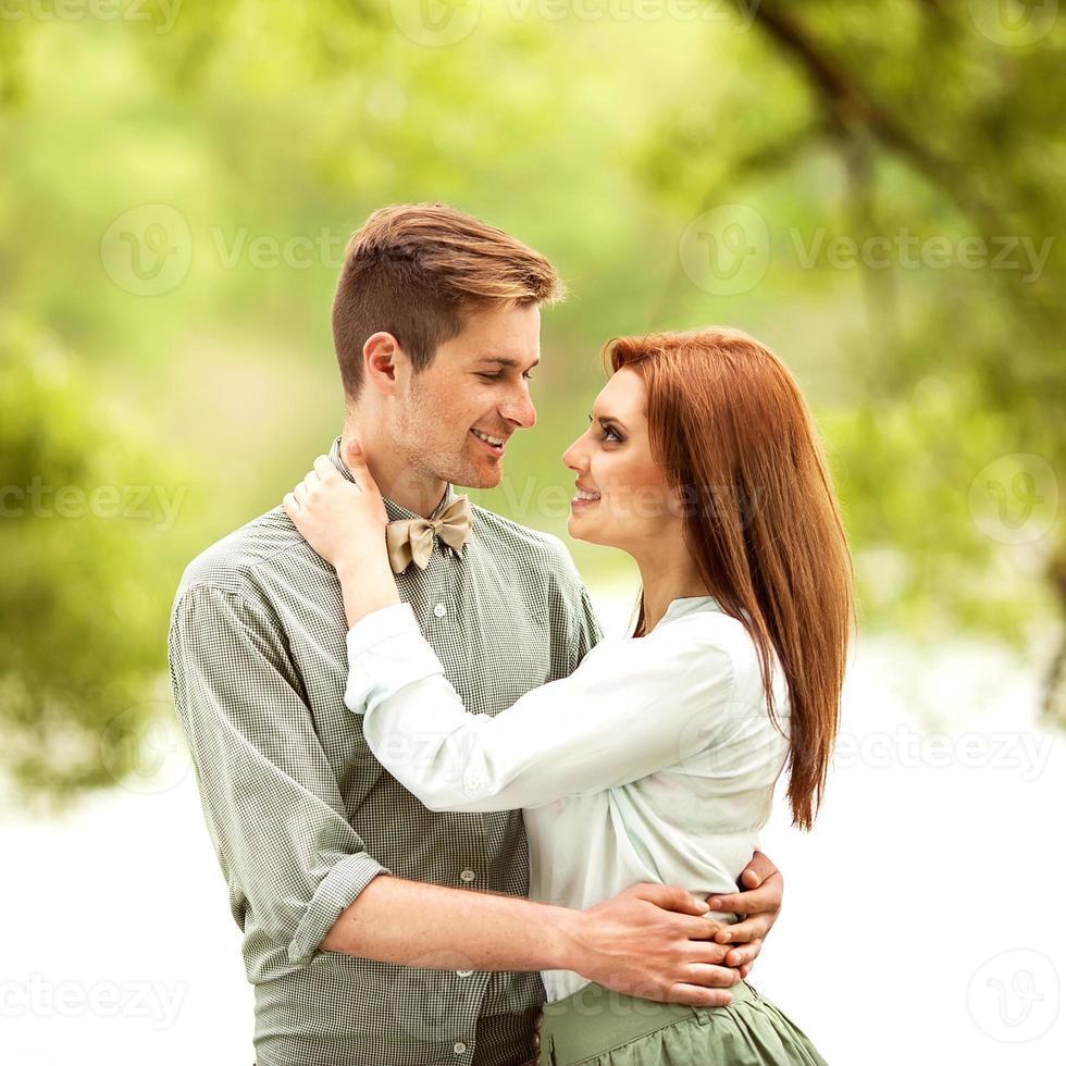 Paar verliebt in Park lächelnd, der einen Blumenstrauß hält foto