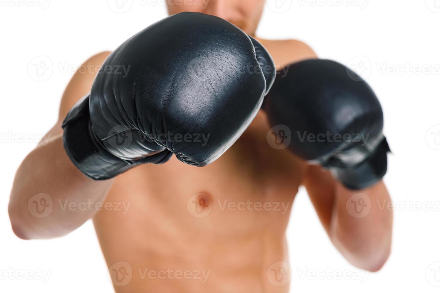 sportlicher Mann, der Boxhandschuhe auf dem Weiß trägt foto