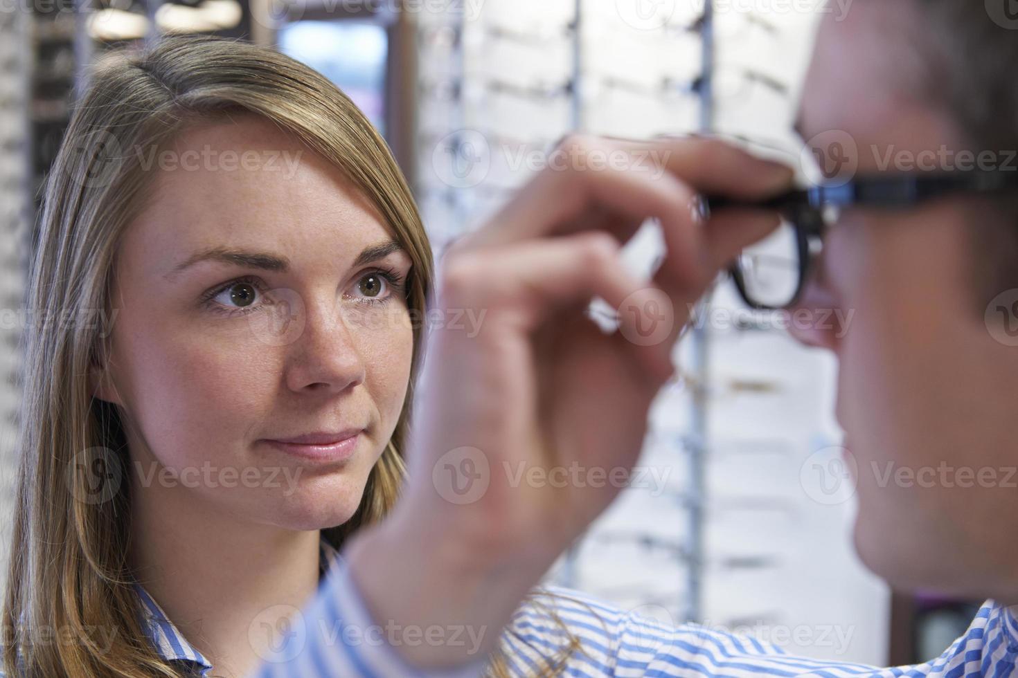 Optiker berät den Kunden bei der Auswahl der Brille foto