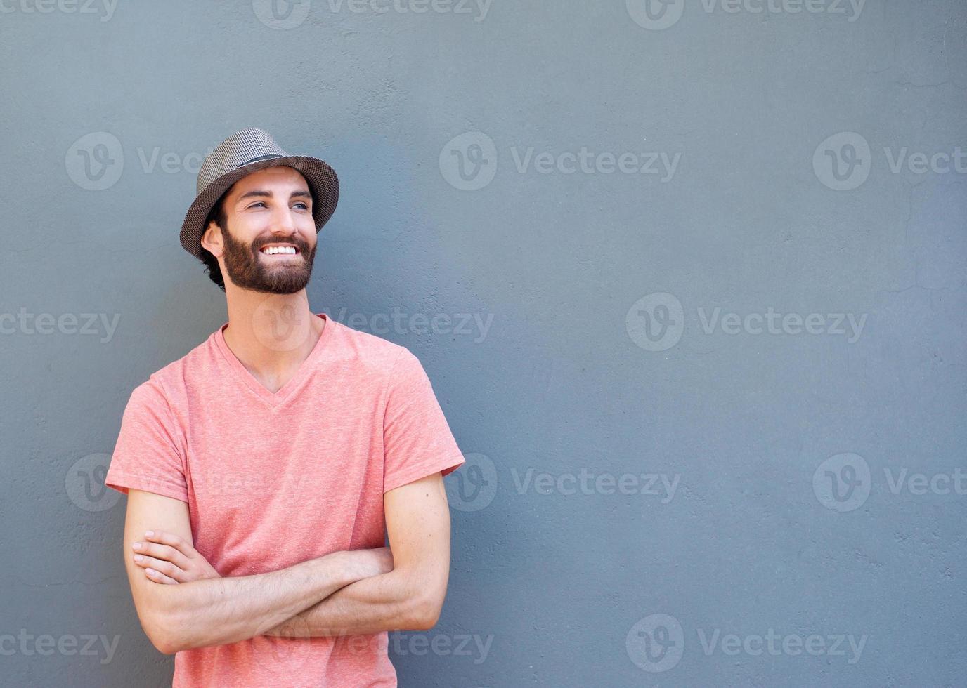 attraktiver junger Mann, der mit verschränkten Armen lächelt foto