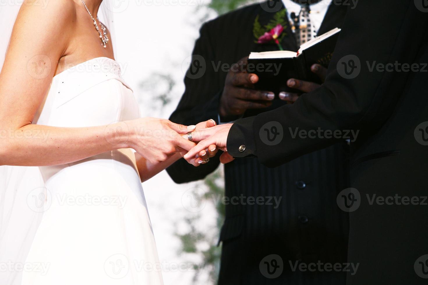 horizontales Porträt der Braut, die Ring auf Bräutigam setzt foto