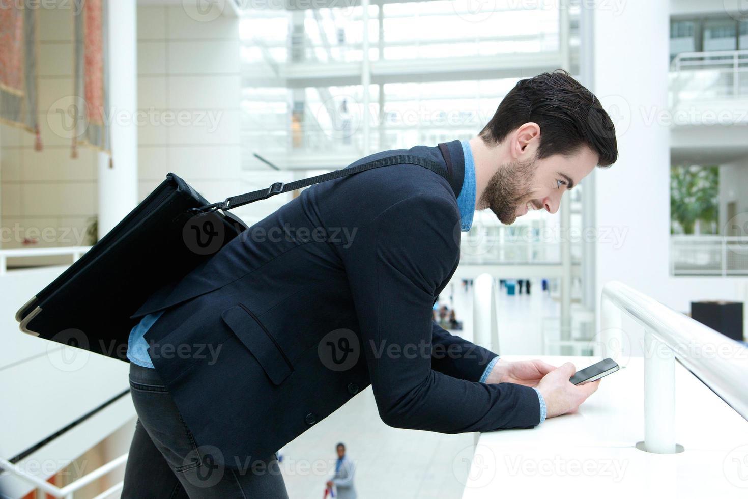 junger Geschäftsmann, der Textnachricht sendet foto