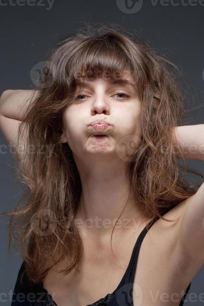 junge Frau mit braunen Haaren, die ein Gesicht machen foto