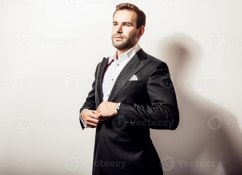 eleganter junger hübscher Mann im klassischen schwarzen Kostüm. foto