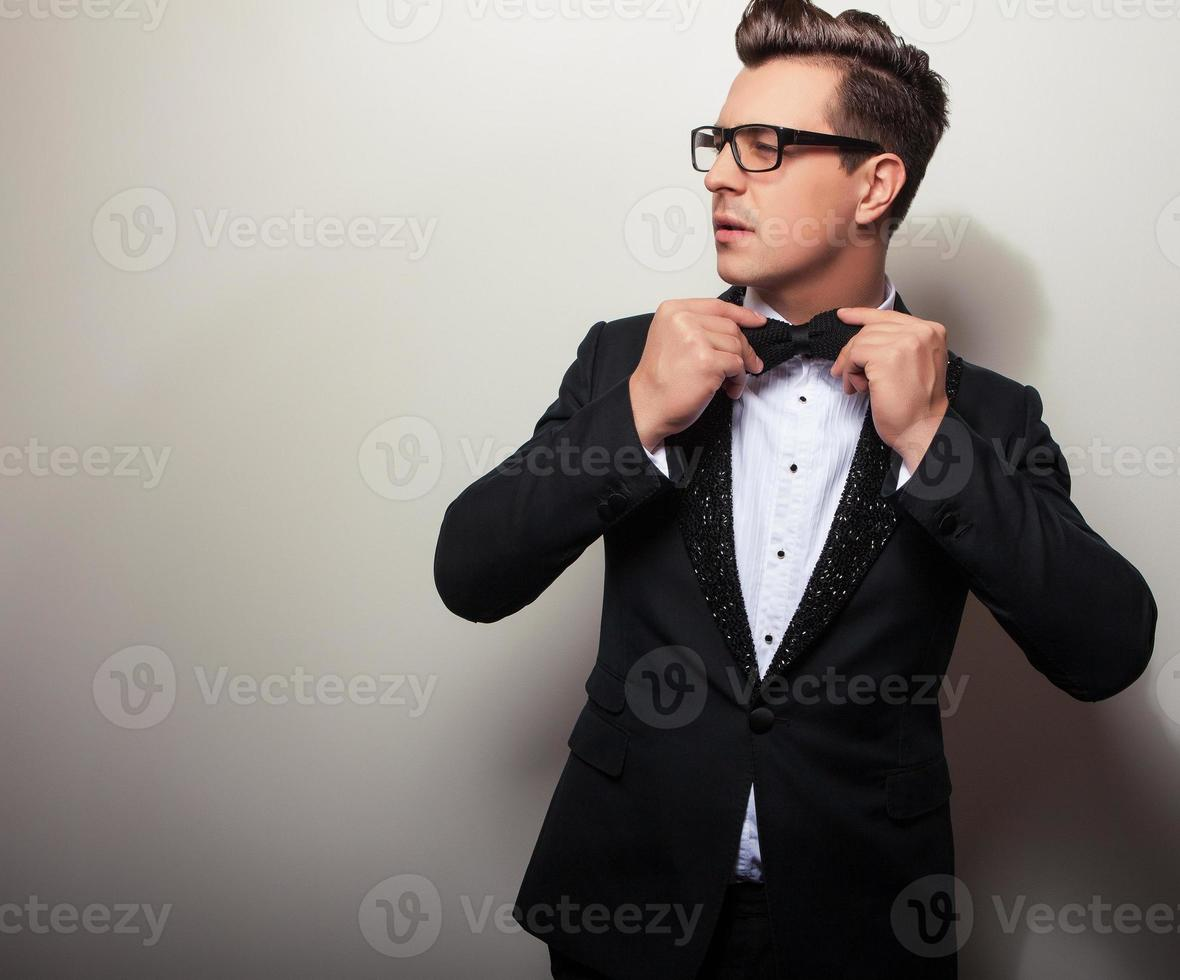 eleganter junger hübscher Mann im schwarzen Luxuskostüm. foto