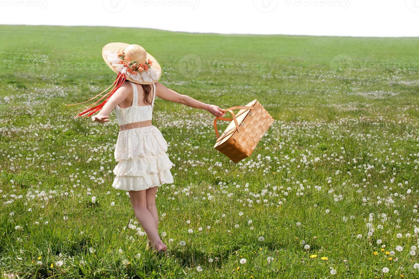junge Frau, die im Grasfeld mit Picknickkorb geht foto
