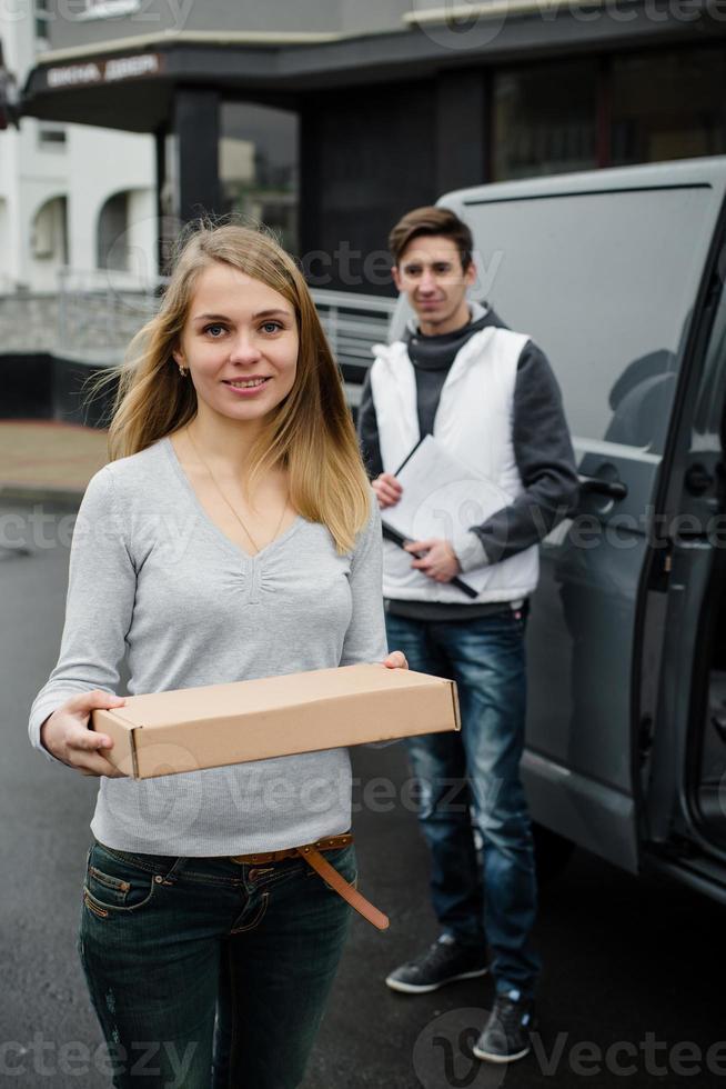 Zufriedener Kunde erhält Postpaket vom Zusteller foto