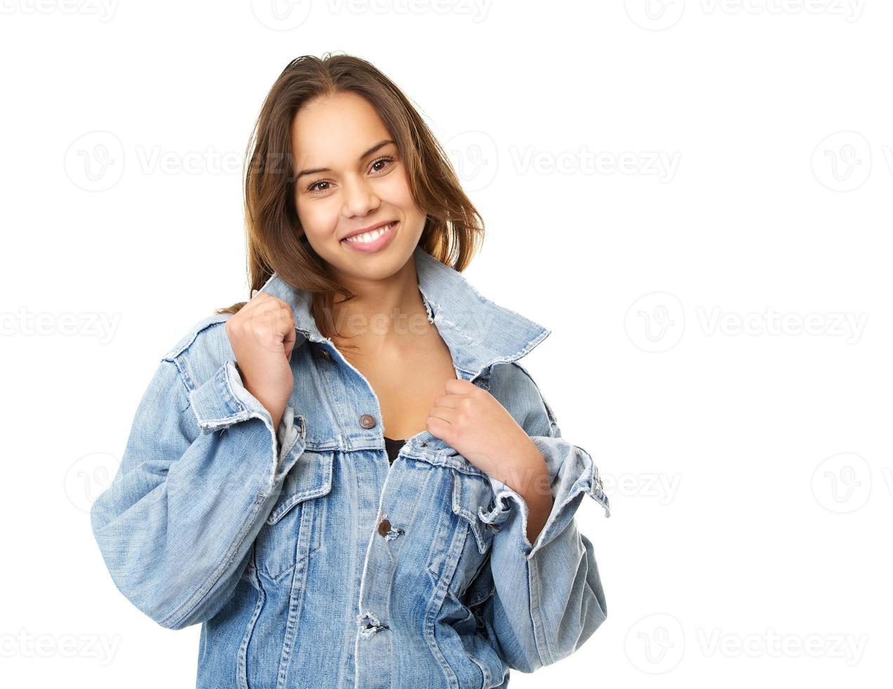 Porträt einer jungen Frau lächelnd und Jeansjacke haltend foto
