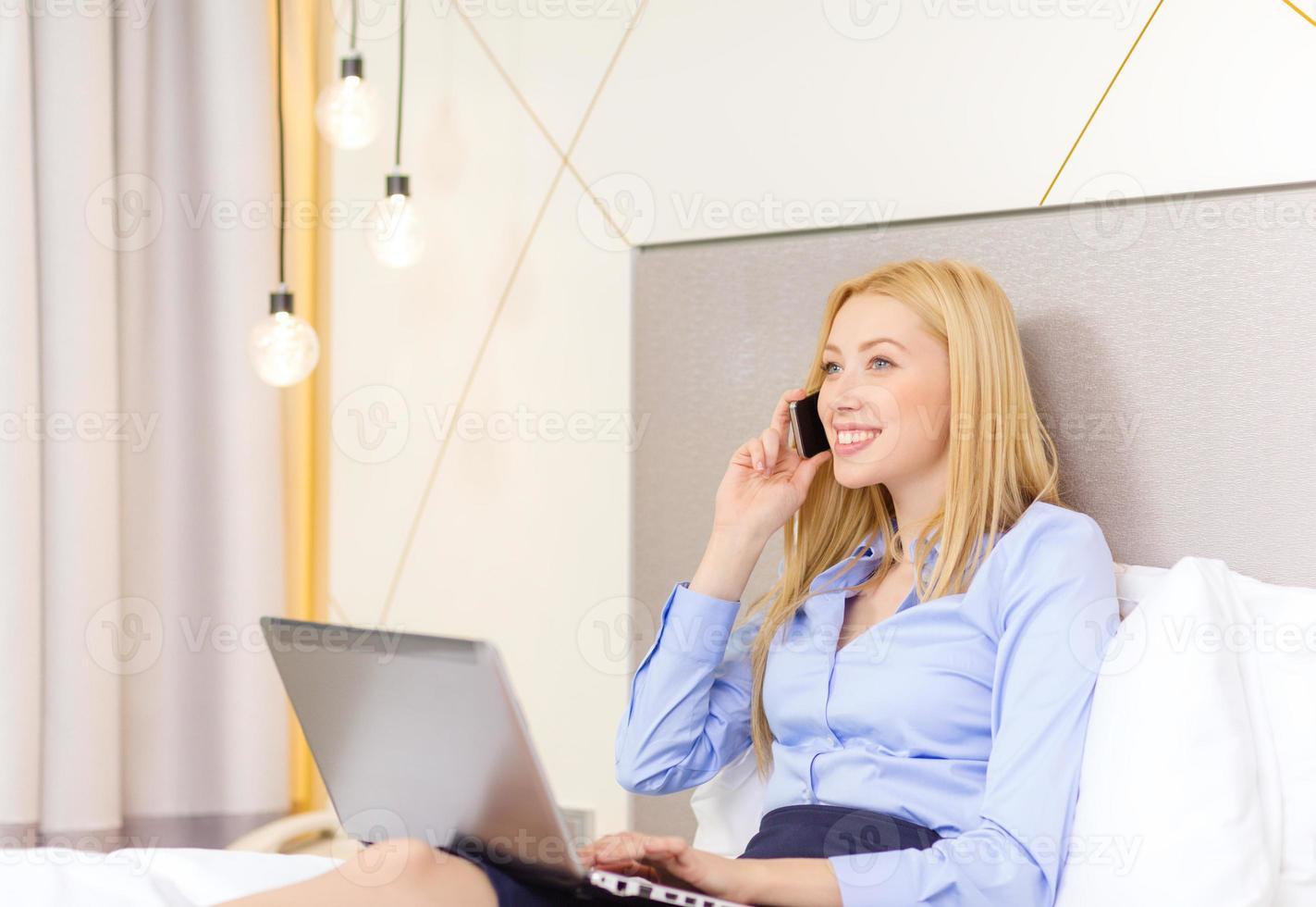 glückliche Geschäftsfrau, die auf Smartphone im Hotel anruft foto