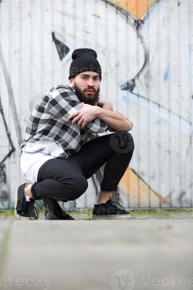 städtischer Mann, der durch Graffiti sitzt foto