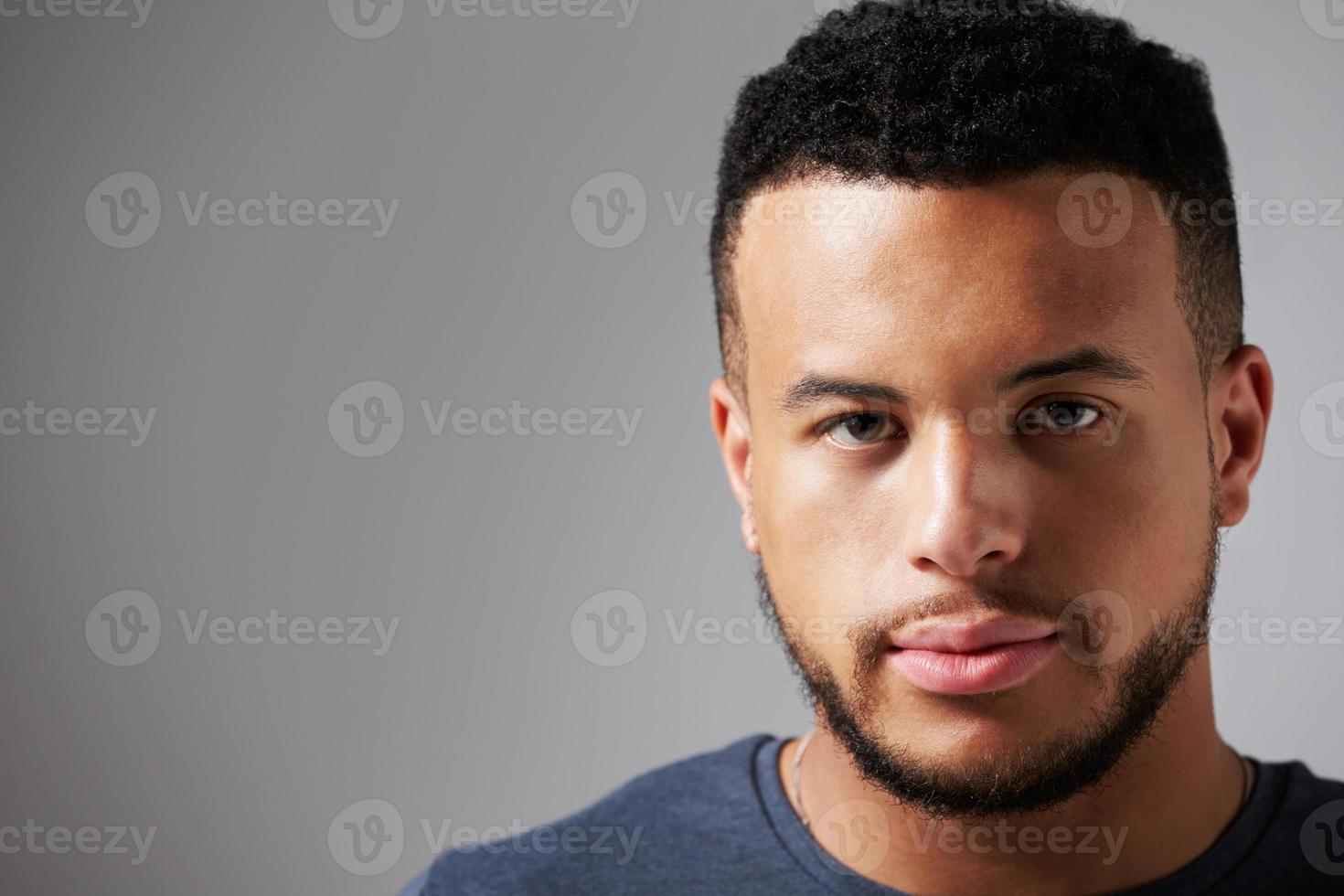 Studioporträt des Mannes, der gegen grauen Hintergrund steht foto