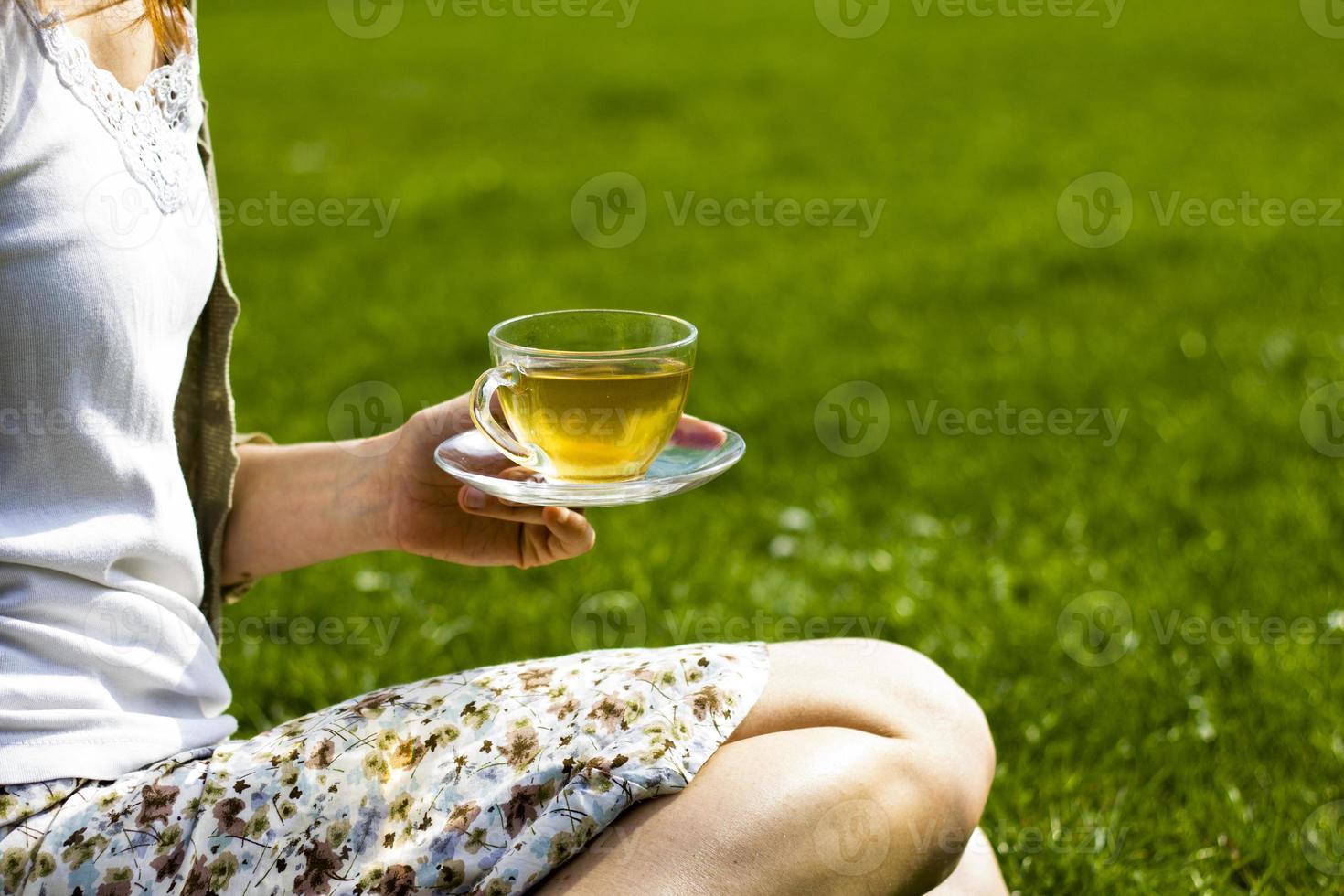 junge Frau, die Tee im Park trinkt foto