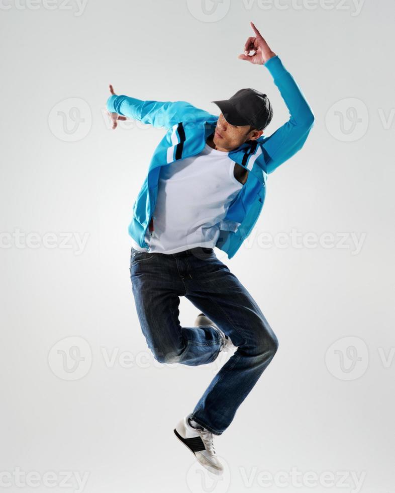 Mann in blauer Jacke tanzt und springt in die Luft foto