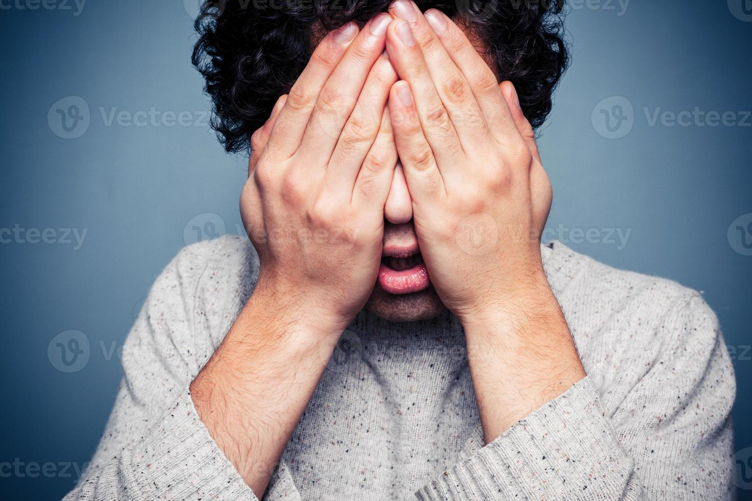 junger Mann versteckt seinen Kopf in Händen foto