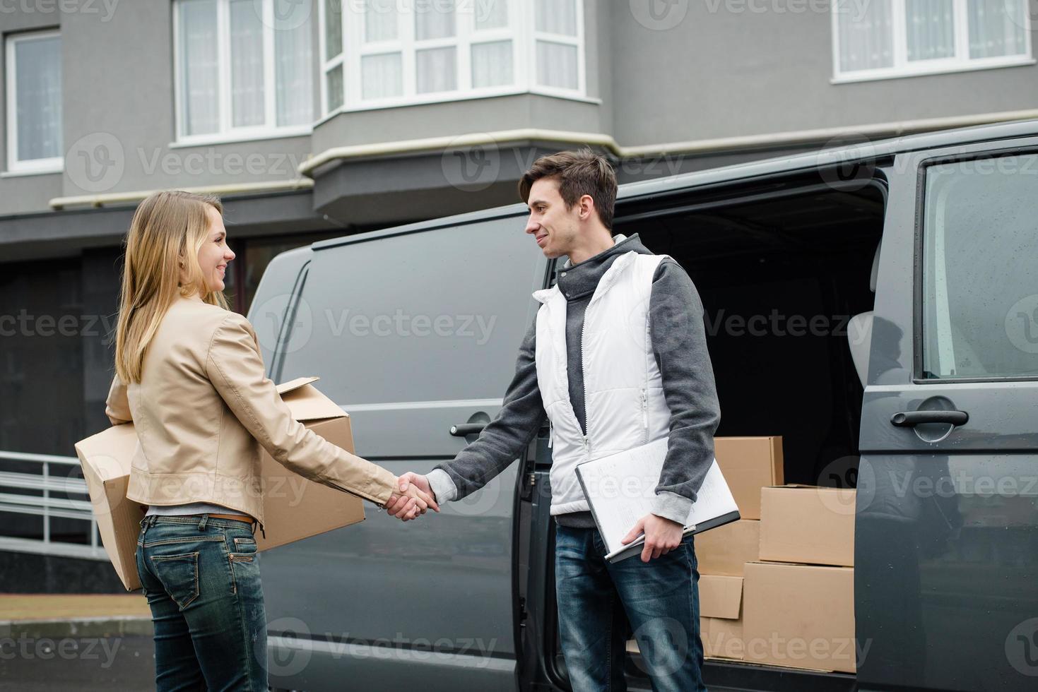 Kurier Händeschütteln in der Nähe des Lieferwagens, Frau erhält Box foto