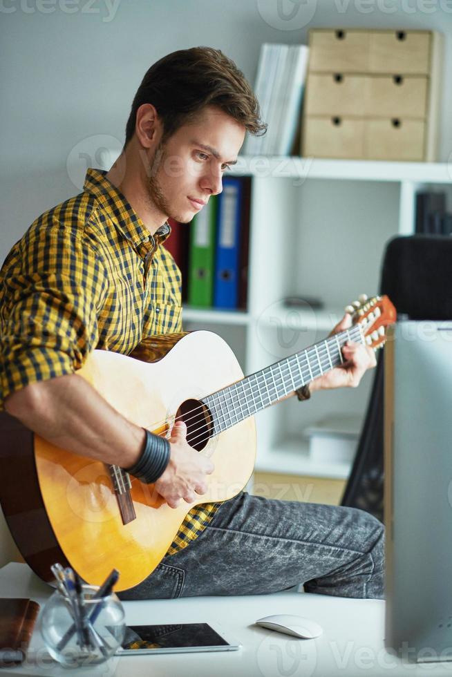 junger Mann, der auf einem Tisch sitzt und Gitarre spielt foto