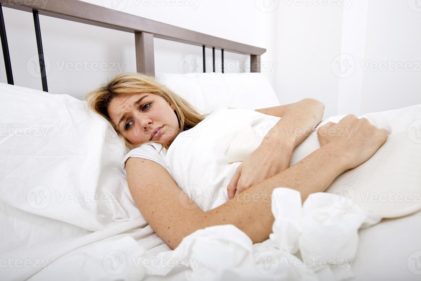 Frau leidet unter Bauchschmerzen im Bett foto